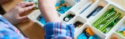 Person sortiert LEGO-Steine auf einem weißen Tablett