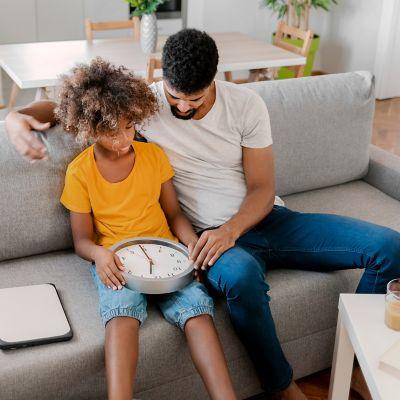 Ojciec uczy syna, jak odczytać godzinę z zegara