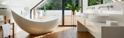 Weiße Badewanne in Bad mit Holzboden