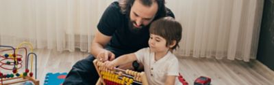Ein Vater bringt seinem Sohn mit Hilfe von Spielzeug das Zählen bei