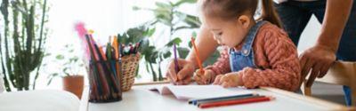 Ein Vater zeigt seinem Kind, wie man einen Stift hält