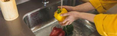 Eine Person wäscht Paprikaschoten