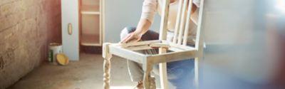 Frau beim Abschleifen eines alten Holzstuhls