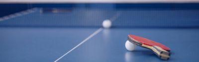 Tischtennisschläger und Tischtennisball auf einem Tischtennistisch