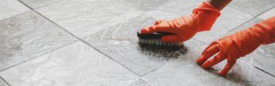 Osoba nosząca czerwone rękawiczki czyszcząca podłogę w łazience