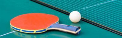 Schläger und Ball auf einem Tischtennistisch