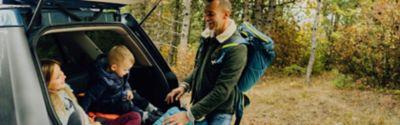 Vater und Kinder am Kofferraum