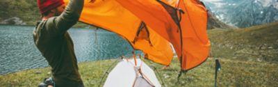 Person, die ein gelbes Zelt aufstellt