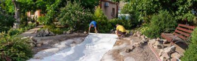 Eine Frau füllt ihren Gartenteich mit Wasser