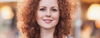 Woman with red curly hair smiling