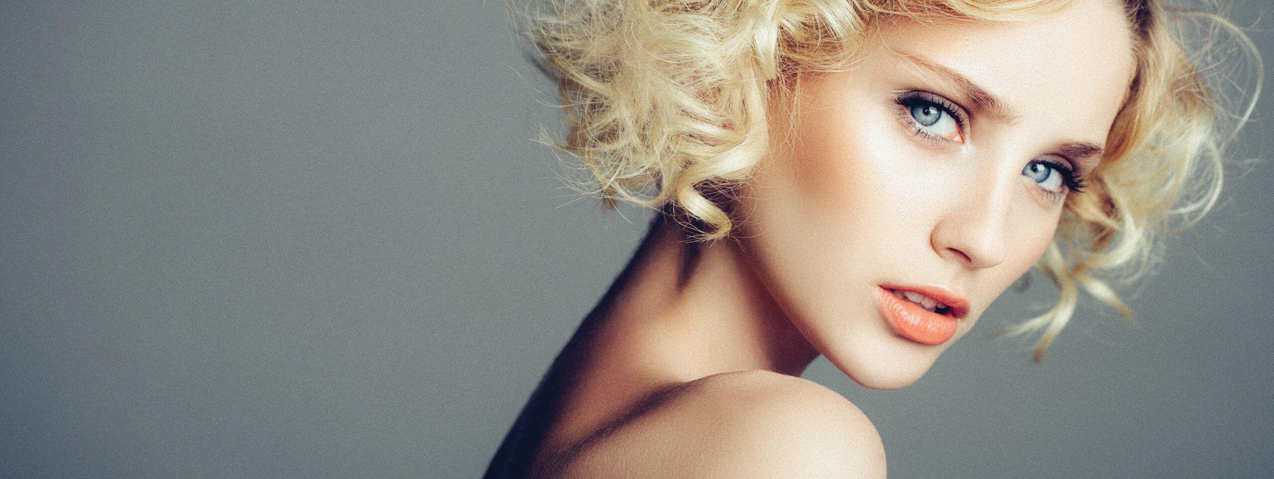 Model wears blonde hair in soft wavy hairstyle