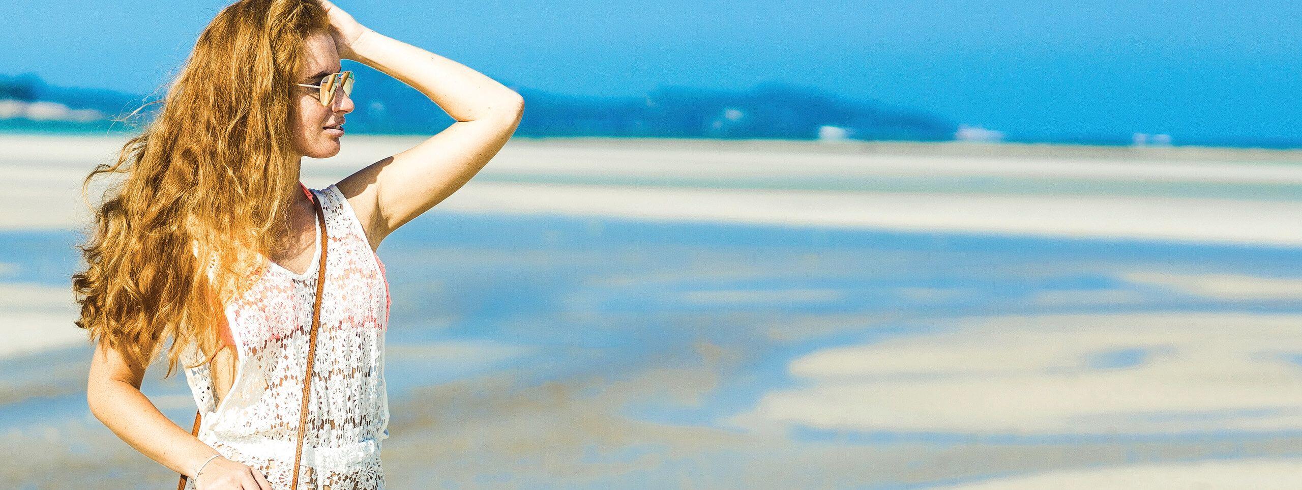 Ragazza sulla spiaggia con capelli beach waves