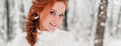 Beautiful young woman with long red hair in winter