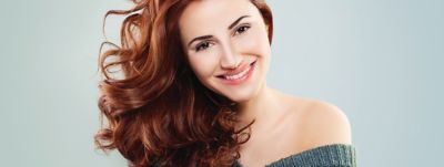 Nice young woman with long red brown hair smiling