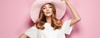 woman with hat on pink background
