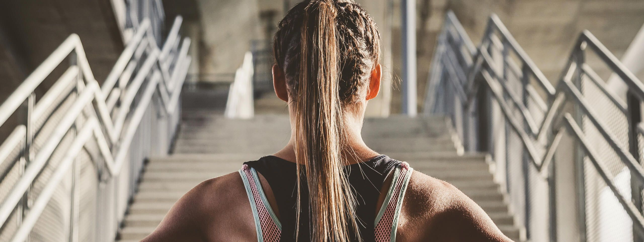 Woman wears high ponytail hairstyle whilst working out