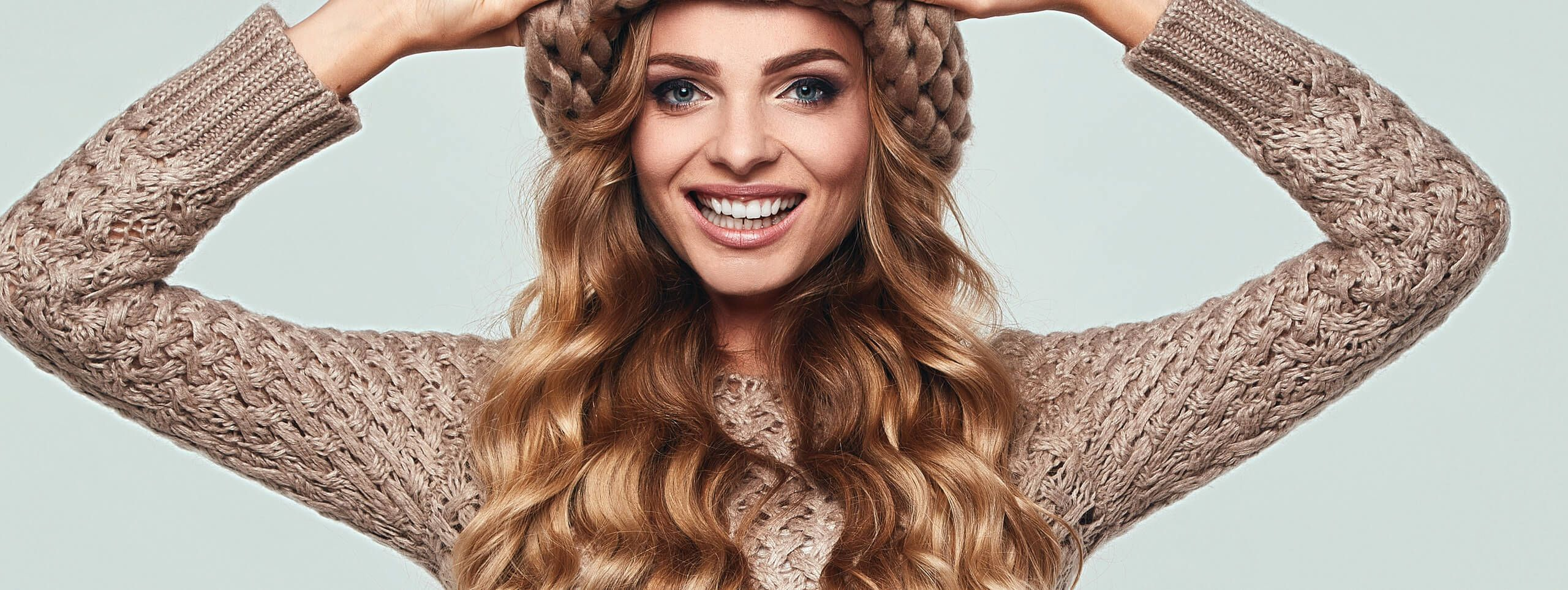 Woman wears brown wavy hairstyle under winter hat