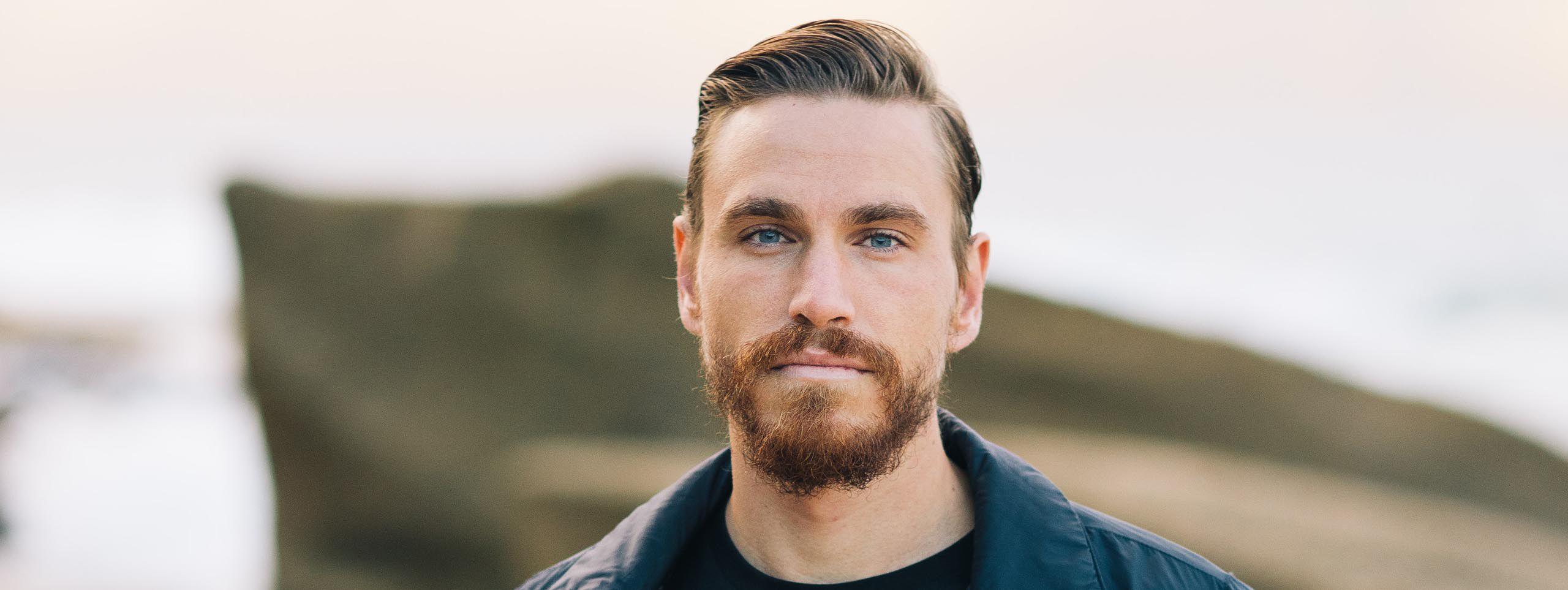 Moški v modri jakni s temno blond lasmi in pet dni staro brado.
