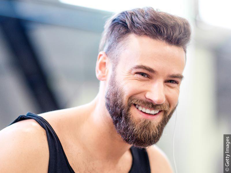 Nasmejan moški s temno blond barvo las v športni majici z lepo urejeno razkošno polno brado.