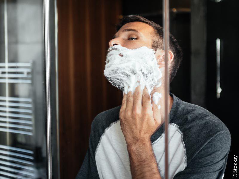 Moški, ki si pred ogledalom nanaša peno za mokro britje.
