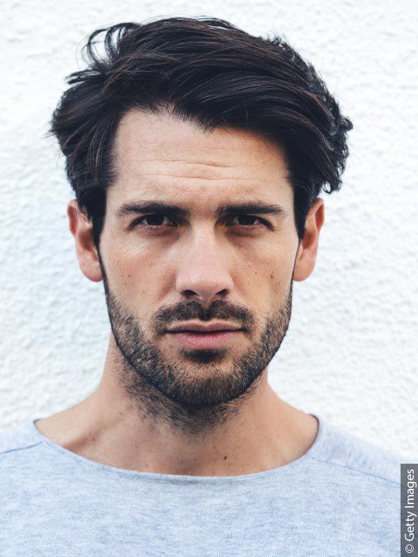 Moški s temnimi lasmi in urejeno tridnevno brado v sivi majici.