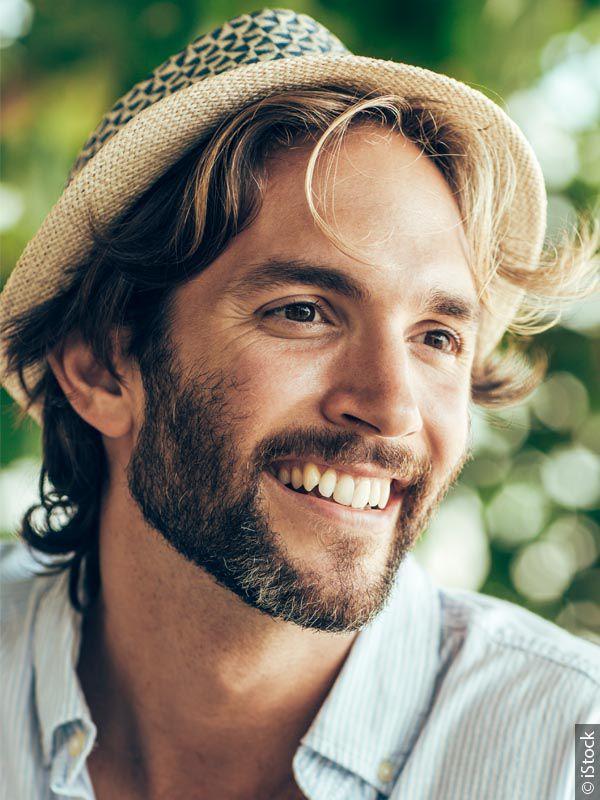 Nasmejan moški s temno blond barvo las in pet dni staro brado, ki nosi klobuk in sedi zunaj v naravi.