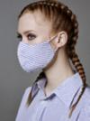Rothaarige Frau trägt Dutch Braids und eine gestreifte Maske passend zur Bluse