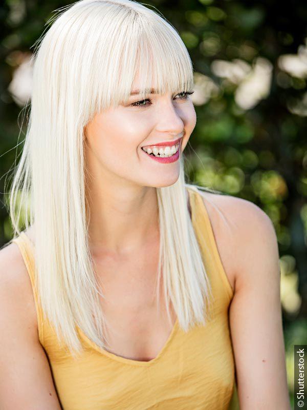 Nasmejana žena sa ravnom, plavom kosom i dugim, ravnim šiškama koja nosi žuti top