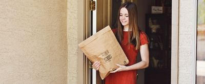 Mujer recogiendo un paquete en el porche delantero