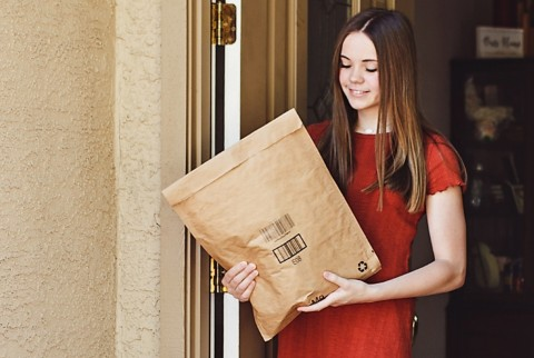 Một khách hàng nữ nhận gói hàng trước hiên nhà