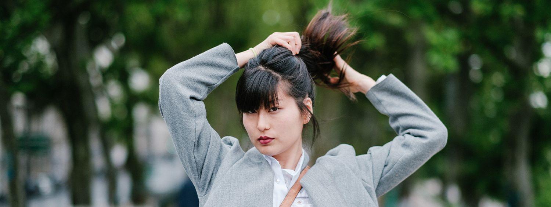 Donna vista di fronte che lega i capelli in una coda di cavallo