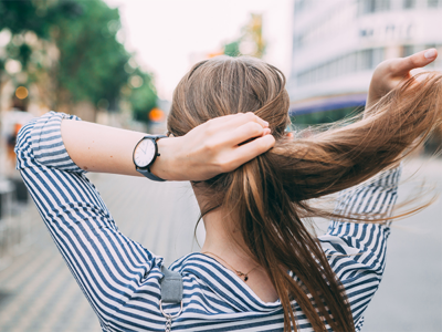 Girl in stripey shirt putting her long hair into a ponytail
