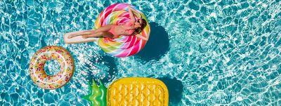 Woman enjoys being in a pool sunbathing on a lollipop shaped floating rubber