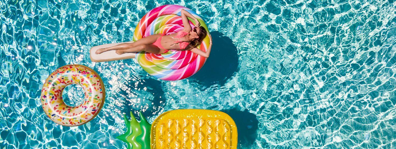 Giovane donna castana sul materassino in piscina