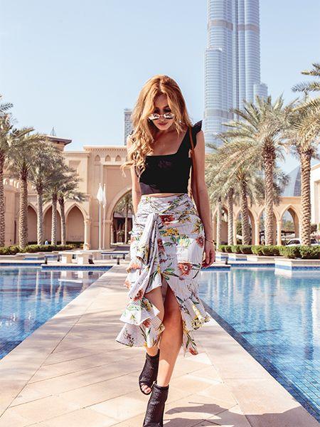 Donna bionda che cammina lungo i bordi della piscina in un abito estivo