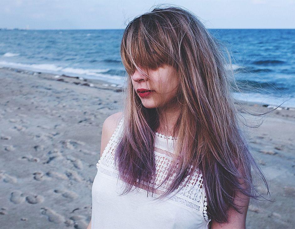 Une femme aux cheveux longs sur une plage avec une frange qu'elle a laissé pousser.