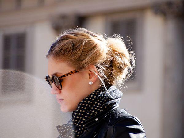 Profil de femme blonde avec une frange tressée et des lunettes de soleil.