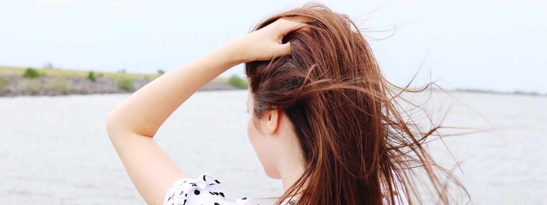 Giovane donna dai capelli rossi davanti a un lago si accarezza i lunghi capelli