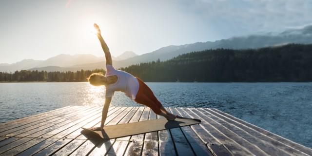 湖边的木桥上,女子在瑜伽垫上练习瑜伽,背景带有阳光。