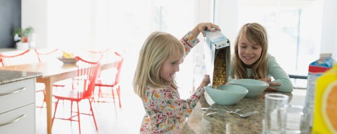 sisters pouring cereal in the kitchen