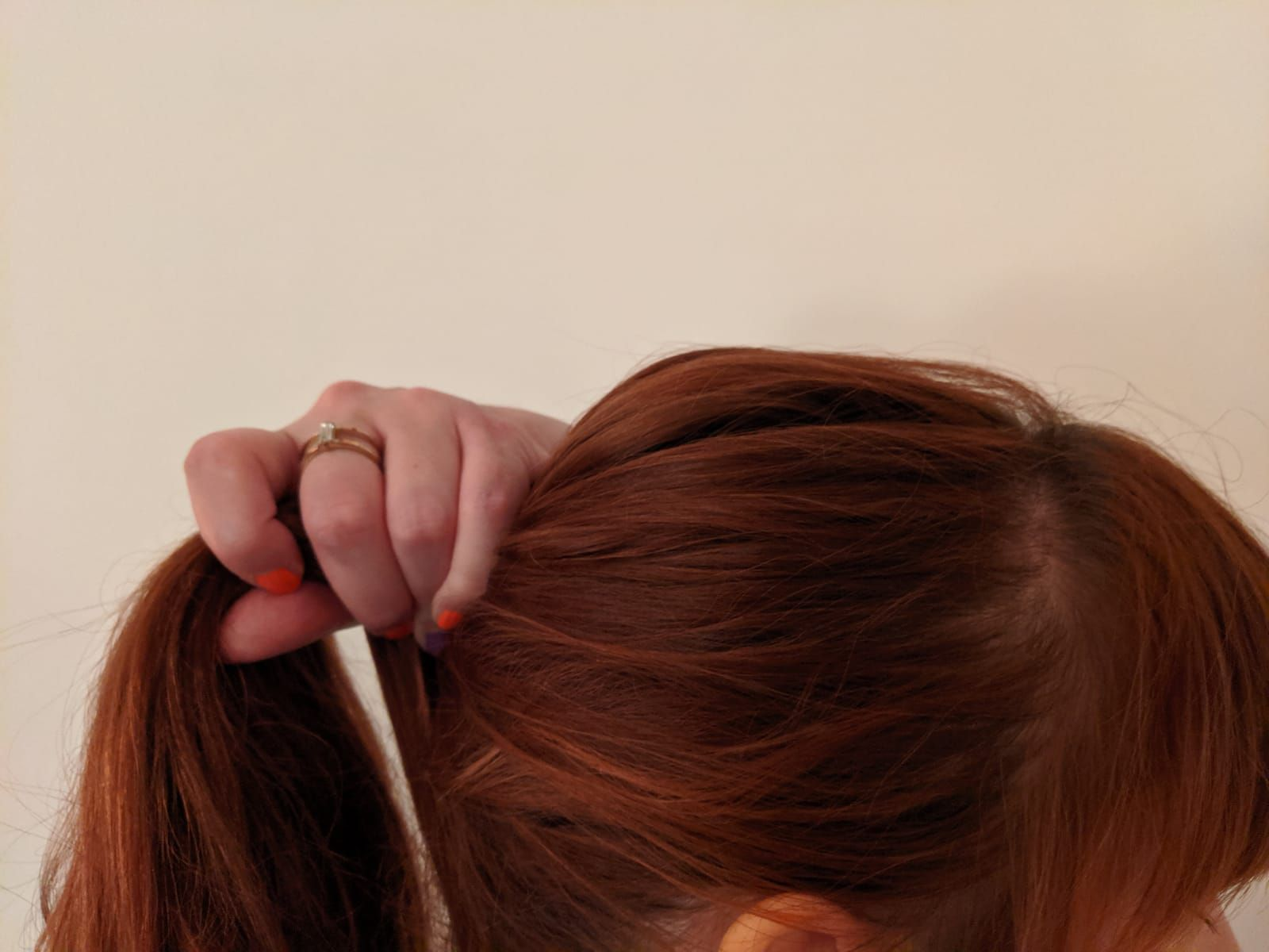Red-haired woman making a ponytail