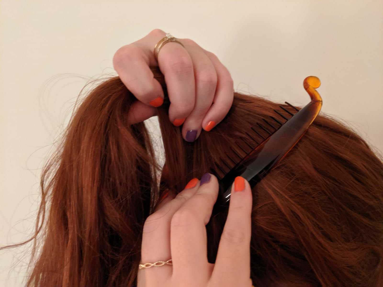 Red-haired woman pushing a banana clip into her hair