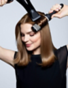Brunette woman blow-drying her hair with a round brush