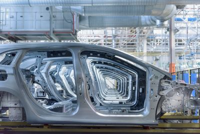 Row of vehicle body in white shell from a side view in a manufacturing facility
