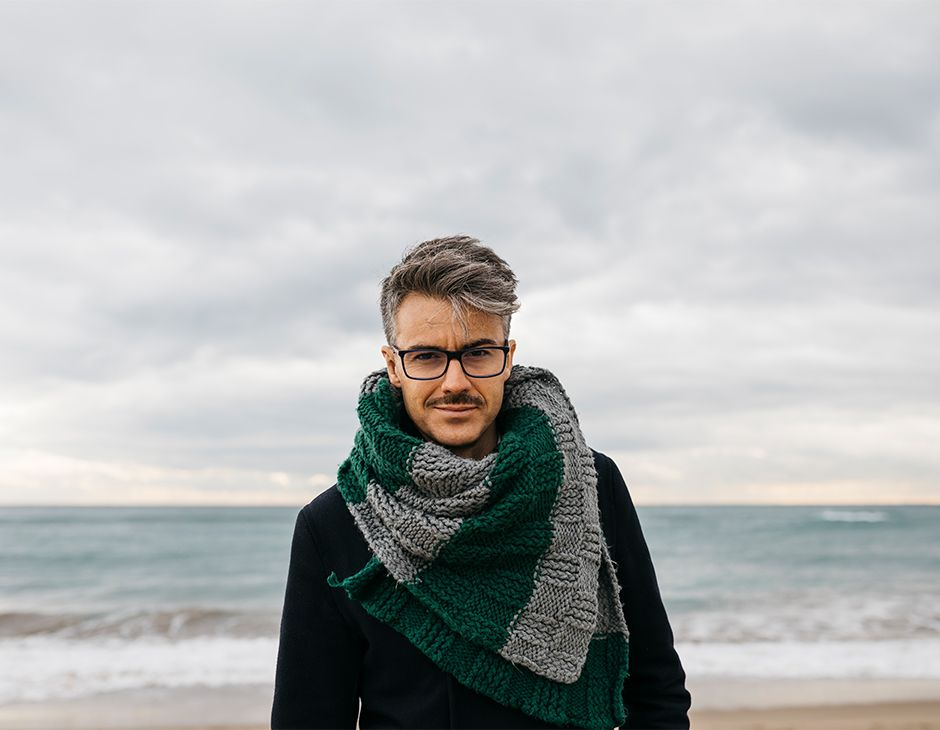 Man with moustache and oversized scarf on the beach
