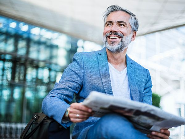 Man with moustache and beard reading the newspaper
