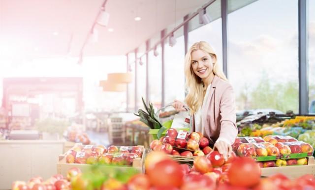 一位女士正在选购贴有标签的苹果