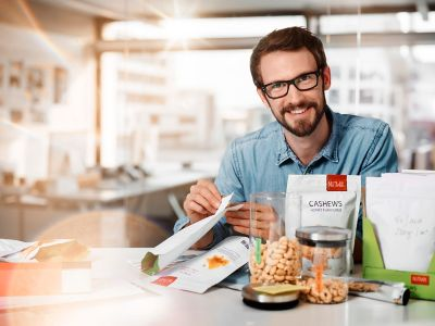 packaging product designer sitting at his working place with a nuts stand-up pouch in his hands