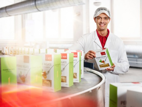 production line manger standing next to a line with manufactured pasta paper cartons with window