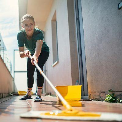 Putzen des Fliesenfußbodens auf Terrasse oder Balkon